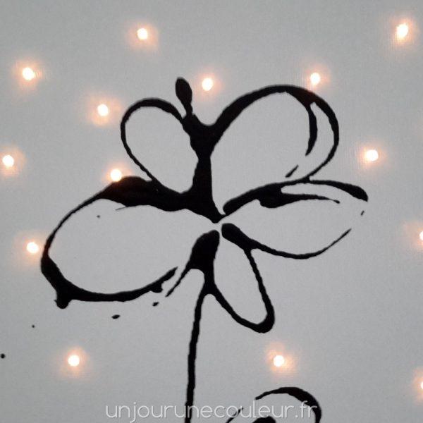 Fleur noire sur tableau lumineux