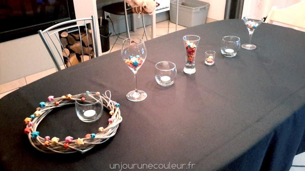 Décoration de table bougies et étoiles colorées dans des verres