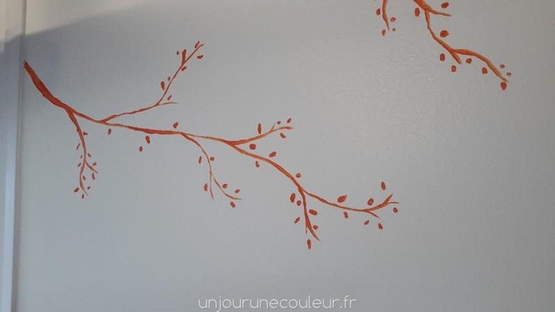 peinture à la main : branche orange sur un mur blanc